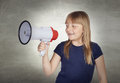 Beautiful girl with blond hair shouting on megaphone and a gray background Royalty Free Stock Photo