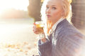 Beautiful girl blonde in warm sweater drinking tea in the Park on a Sunny autumn day in the bright rays of the sun Royalty Free Stock Photo
