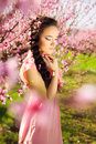 Beautiful girl in blossomy garden young peach with flowers braid elegantly touching her chin by hand Stock Photo