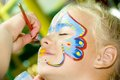 Beautiful girl blue eyes painted butterfly her face Stock Photos