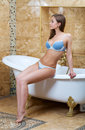 Beautiful girl in blue underwear in the bathroom sitting on a luxurious white bath Royalty Free Stock Images