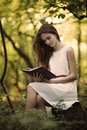 Beautiful girl with book in the forest young Stock Images
