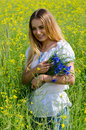 Beautiful girl with bouquet of cornflowers on flowering rapeseed