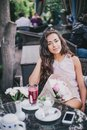 Beautiful girl with a bouquet of peonies sitting in a restaurant drinking berry tea Royalty Free Stock Photography