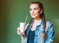Beautiful girl with braids sitting in a cafe and drinking a milkshake looking out the window super Stock Photos