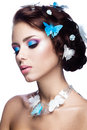 Beautiful girl with bright blue makeup and butterflies in her hair.
