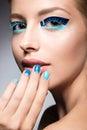 Beautiful girl with bright creative fashion makeup and blue nail polish. Art beauty design. Royalty Free Stock Photo