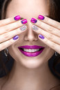 Beautiful girl with a bright evening make up and purple manicure with rhinestones nail design beauty face picture taken in the Royalty Free Stock Image
