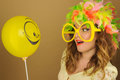 Beautiful girl in a bright wig and big glasses holding a balloon on the background Royalty Free Stock Images