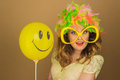 Beautiful girl in a bright wig and big glasses holding a balloon on the background Royalty Free Stock Photography