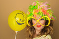 Beautiful girl in a bright wig and big glasses holding a balloon on the background Stock Photo
