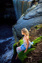 Beautiful girl on brink of river waterfalls Royalty Free Stock Image