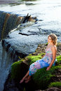 Beautiful girl on brink of river waterfalls Stock Photo