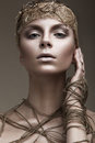 Beautiful girl with a bronze skin, pale makeup and unusual accessories. Art beauty image. Beauty face. Royalty Free Stock Photo