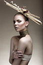 Beautiful girl with a bronze skin, pale makeup and unusual accessories. Art beauty image. Beauty face.