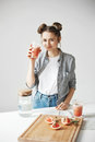 stock image of  Beautiful girl with buns smiling drinking grapefruit detox smoothie to camera over white wall. Healthy diet nutrition
