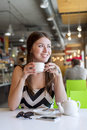Beautiful girl in a cafe drinking tea, coffee, breakfast the restaurant looking out into street Royalty Free Stock Photo