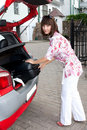 Beautiful girl in a car trunk loads, a big, heavy, Stock Photo