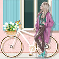 Beautiful girl in casual clothes with bicycle and building facade.