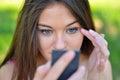 Beautiful girl checking her makeup outdoor this image represents Stock Photos