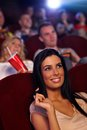 Beautiful girl in cinema smiling young sitting playing with hair Stock Photography