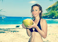 Beautiful girl with coconut on background of sea, Royalty Free Stock Photo