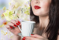 Beautiful girl with a cup of green tea buds orchids best tradition Stock Photography