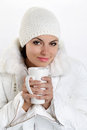 Beautiful girl with cup in hands to keep warm drink on white background Stock Photo