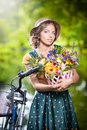 Beautiful girl with cute hat and basket with flowe flowers having fun in park bicycle healthy outdoor lifestyle concept vintage Stock Photography