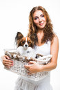 Beautiful girl with cute papillon dog on isolated white young in basket background Stock Image