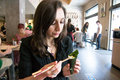 Beautiful girl with dark hair, dressed in black is holding chopsticks and temaki sushi