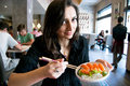 Beautiful girl with dark hair, dressed in black is holding a plate full of sushi