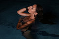 Beautiful girl with dark hair posing in night swimming pool Royalty Free Stock Photo