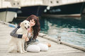 Beautiful girl with a dog on the pier in the summer her near sea portrait of young her Royalty Free Stock Images