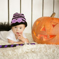 Beautiful girl with Down syndrome thoughtfully keeps finger in the mouth near the big pumpkin Royalty Free Stock Photo