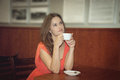Beautiful girl dreams young brunette sitting at a table with cup of coffee Royalty Free Stock Image
