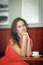 Beautiful girl dreams young brunette sitting at a table with cup of coffee Royalty Free Stock Images