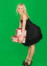 Beautiful girl in a dress with gifts on green background Stock Image
