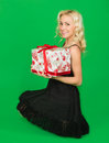 Beautiful girl in a dress with gifts on green background Royalty Free Stock Image