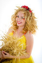 Beautiful girl dressed yellow with wheaten ears red haired freckles in an image of hot summer Royalty Free Stock Image