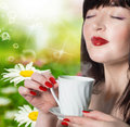 Beautiful girl drinking tea coffee over green nature background Royalty Free Stock Image