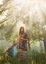 Beautiful girl eastern appearance walking at hte forest fields at sunset fashionable toning creative color Royalty Free Stock Image