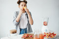 Beautiful girl eating grapefruit piece over white wall. Healthy fitness nutrition. Copy space.
