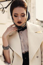 Beautiful girl in elegant beige coat and silk scarf on head fashion outdoor photo of lady wearing luxurious her Royalty Free Stock Image