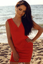 Beautiful girl in elegant red dress relaxing on summer beach Royalty Free Stock Photo