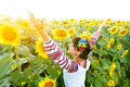 Beautiful girl in embrodery rise hands up on a sunflower plant Royalty Free Stock Photo