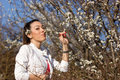 Beautiful girl enjoys the outdoors in spring smelling wild cherry flower Stock Images