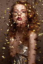Beautiful girl in an evening dress and gold curls. Model in New Year`s image with glitter and tinsel. Royalty Free Stock Photo