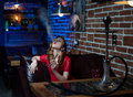 Beautiful girl in evening dress smokes a hookah in the interior of the bar Royalty Free Stock Photo