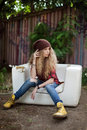 Beautiful girl in fashionable clothes on a broken couch Royalty Free Stock Photo